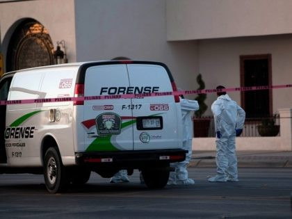 Mexican forensic personnel wait outside an exclusive restaurant in Ciudad Juarez, Chihuahua state, Mexico on May 07, 2013, after four men were killed inside the facilitiy by a gang armed with AK-47 assault rifles. AFP PHOTO/JESUS ALCAZAR (Photo credit should read Jesus Alcazar/AFP/Getty Images)