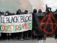 Protestors dressed in black and with the face covered hold smoke bombs and a banner reading 'The Black bloc colours our lives' and depicting the Anarchist symbol as they take part in a march for the annual May Day workers' rally, in Paris, on May 1, 2018. (Photo by Thomas …