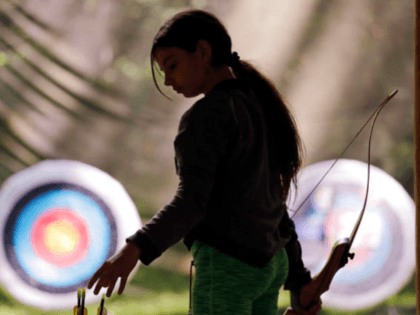 Ket Davis reaches for an arrow during an archery session at a Girl Scout day camp in Carnation, Wash., on Tuesday, June 26, 2018. (AP Photo/Elaine Thompson)