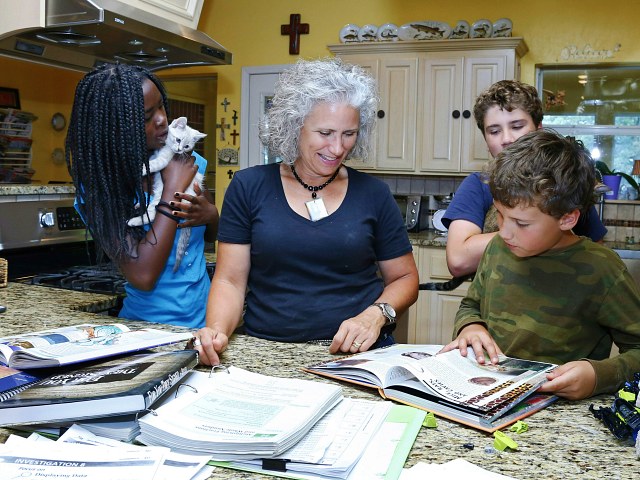 Jenni White, second from left, works with her son and third-grade student, Sam White, right, as her other children, sixth graders Betty White, left, and Coleman White, rear, look on, in Luther, Okla., Monday, June 9, 2014. (AP Photo/Sue Ogrocki)