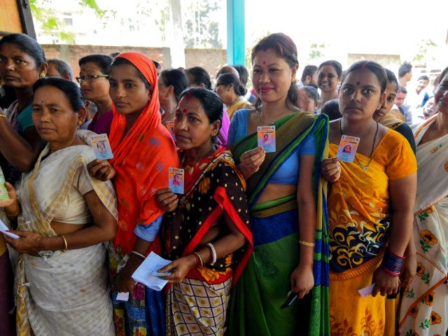 Indian voters show their voter identity cards as they stand in a queue to cast their vote at a polling station during India's general election in Samuguri village, some 140 km from Guwahati, the capital city of Indias northeastern state of Assam on April 11, 2019. - India's mammoth six-week …