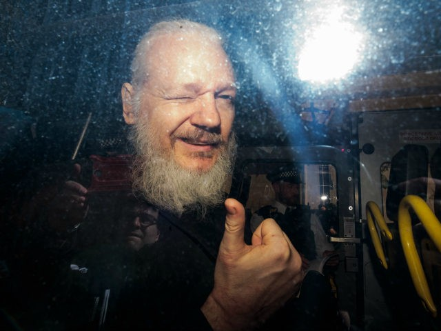 Julian Assange gestures to the media from a police vehicle on his arrival at Westminster Magistrates court on April 11, 2019 in London, England. After weeks of speculation Wikileaks founder Julian Assange was arrested by Scotland Yard Police Officers inside the Ecuadorian Embassy in Central London this morning. Ecuador's President, …