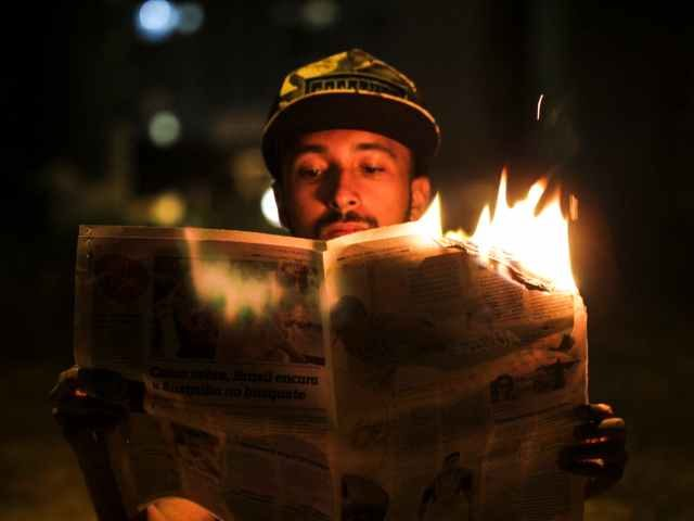 Man reading a burning newspaper