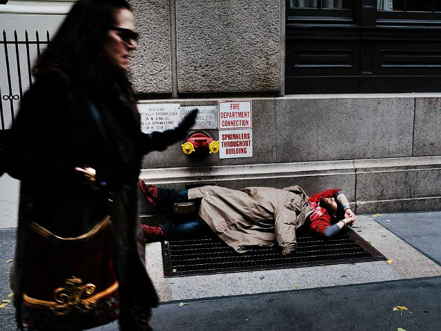 NEW YORK, NY - NOVEMBER 30: A woman walks by a homeless man along a Manhattan street on November 30, 2017 in New York City. Republicans are coming closer to getting the votes needed to pass their proposed tax cut which many economists predict will benefit the wealthy at the …