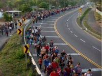 Central American migrants, part of the caravan hoping to reach the U.S. border, walk on the shoulder of a road in Frontera Hidalgo, Mexico, Friday, April 12, 2019. The group pushed past police guarding the bridge and joined a larger group of about 2,000 migrants who are walking toward Tapachula, …