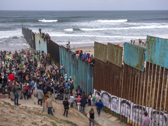 TIJUANA, MEXICO - APRIL 29: People climb a section of border fence to look into the U.S. as members of a caravan of Central American asylum seekers arrive to a rally on April 29, 2018 in Tijuana, Baja California Norte, Mexico. More than 300 immigrants, the remnants of a caravan …