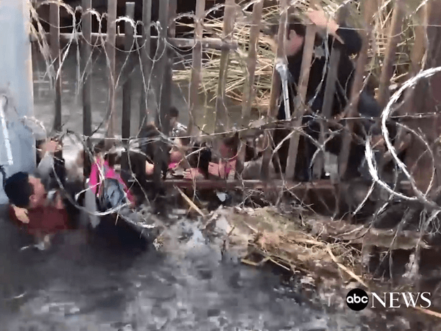 Video published by ABC News shows migrants pushing children under a fence in a water-filled ditch at the Arizona Border. (Photo: ABC NEWS Video Screenshot)