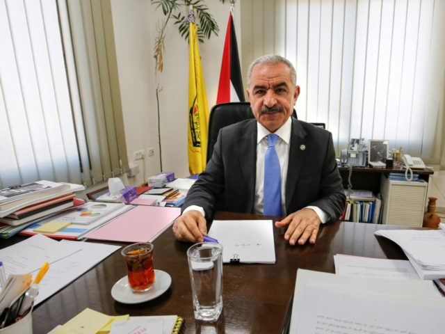 Newly-appointed Palestinian Prime Minister Mohammad Shtayyeh sits behind his desk at his office in the West Bank city of Ramallah on March 10, 2019. - Shtayyeh, born in 1958, a long-term Abbas ally and member of the Fatah central committee, replaces Rami Hamdallah, who was politically independent. An academic and …