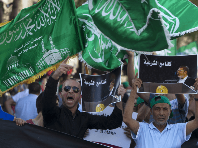 Members of the Arab-Israeli Islamic Movement chant slogans during a protest in support of deposed Egyptian president Mohamed Morsi (portrait) and against the army crackdown on Muslim Brotherhood supporters, in the northern Israeli city of Nazareth on August 17, 2013. AFP PHOTO / AHMAD GHARABLI (Photo credit should read AHMAD …