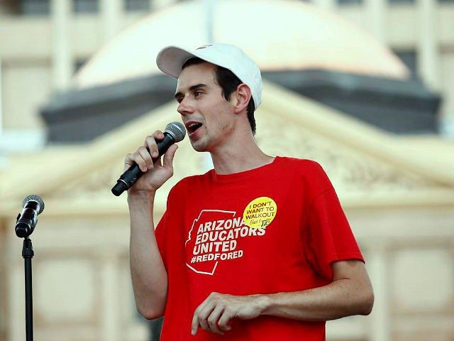Music teacher Noah Karvelis, who helped organize Arizona Educators United, speaks to thousands as they participate in a protest at the Arizona Capitol for higher teacher pay and school funding on the first day of a state-wide teachers strike Thursday, April 26, 2018, in Phoenix. (AP Photo/Ross D. Franklin)