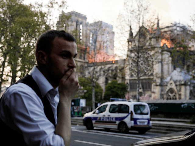 A man reacts as he watches the flames engulf the roof of the Notre-Dame Cathedral in Paris on April 15, 2019. - A huge fire swept through the roof of the famed Notre-Dame Cathedral in central Paris on April 15, 2019, sending flames and huge clouds of grey smoke billowing into the sky. The flames and smoke plumed from the spire and roof of the gothic cathedral, visited by millions of people a year. A spokesman for the cathedral told AFP that the wooden structure supporting the roof was being gutted by the blaze. (Photo by GEOFFROY VAN DER HASSELT / AFP) (Photo credit should read GEOFFROY VAN DER HASSELT/AFP/Getty Images)