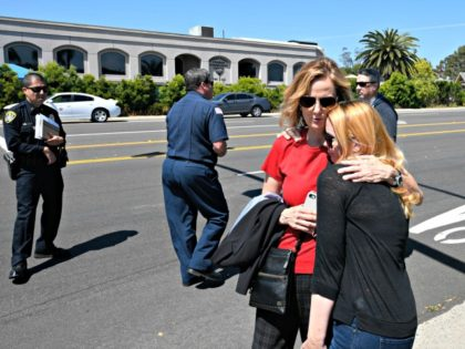 Jessica Parks, right, hugs Tina White outside of the Chabad of Poway Synagogue Saturday, April 27, 2019, in Poway, Calif. Several people were injured in a shooting at the synagogue. (AP Photo/Denis Poroy)