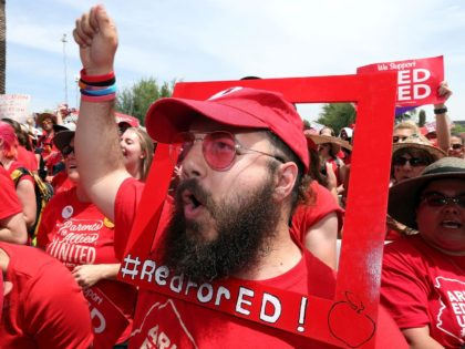 APRIL 26: Aude Odeh, an english teacher at Barry Goldwater High School, cheers in support of the #REDforED movement during a rally in front of the State Capitol on April 26, 2018 in Phoenix, Arizona. Teachers state-wide staged a walkout strike on Thursday in support of better wages and state …