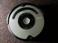 The Roomba vacuum cleaner by iRobot Corp. is seen in Boston on Tuesday, Aug. 21, 2007. Nearly five years after rolling onto the market, the Roomba vacuum cleaner has undergone a ground-up redesign that has endowed the otherwise-brainy robot with the smarts to overcome rug tassels and electrical cords. (AP …