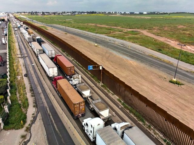 Aerial view of cargo trucks lining up to cross to the United States near the US-Mexico border at Otay Mesa crossing port in Tijuana, Baja California state, Mexico, on April 4, 2019. - US President Donald Trump is expected to visit a section of the border fence in Calexico during …