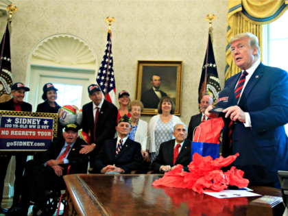 President Donald Trump is presented with a cap by World War II veterans, seated from left, Sidney Walton, joined by fellow WW II veterans Allen Jones, Paul Kriner and Floyd Wigfield, in the Oval Office of the White House in Washington, Thursday, April 11, 2019. (AP Photo/Manuel Balce Ceneta)
