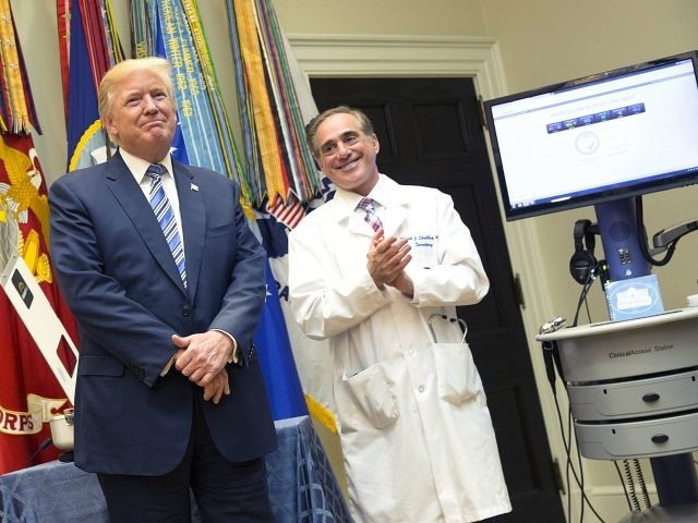 WASHINGTON, DC - AUGUST 3: (AFP OUT) U.S. President Donald J. Trump(left) listens to applause with Veterans Affairs Secretary Dr.David Shulkin(right) at the announcement by the Department of Veterans Affairs outlining a new program using video and software technology to provide medical care to veterans at The White House August …