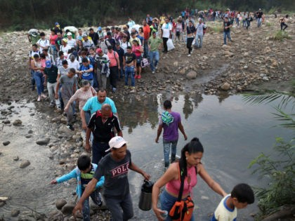 CUCUTA, COLOMBIA - MARCH 02: People cross through the low waters of the Táchira River near the Simón Bolívar international bridge on March 2, 2019 in Cucuta, Colombia. The bridge, which is closed, connects Cúcuta to the Venezuelan town of San Antonio del Táchira. Many people are making the trek …