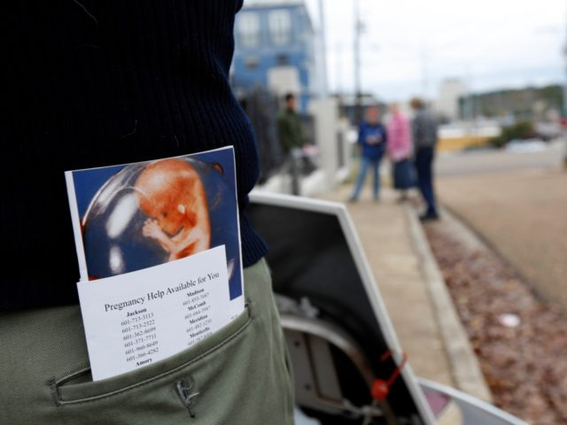 An abortion foe carries a graphic brochure showing a fetus during its growth pattern which he and other abortion foes attempt to give women entering and leaving the Jackson Women's Health Organization Inc., Mississippi's only commercial abortion clinic in Jackson, Miss., Friday, Jan. 11, 2013. The facility missed a Friday …
