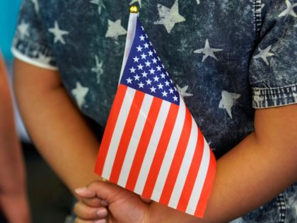 SALT LAKE CITY, UT - APRIL 10: A school child holds an American Flag behind his back at a Naturalization Ceremony on April 10, 2019 in Salt Lake City, Utah. There were 49 people from 26 countries that became U.S. citizens. A group of Republican Senators are introducing a bill …