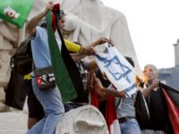 Pro-Palestinian demonstrators burn an Israeli national flag after climbing on the Republic monument, on the Republique square in Paris, during a banned demonstration against Israel's military operation in Gaza and in support of the Palestinian people, on July 26, 2014. French authorities banned on July 26, 2014 a new pro-Palestinian …