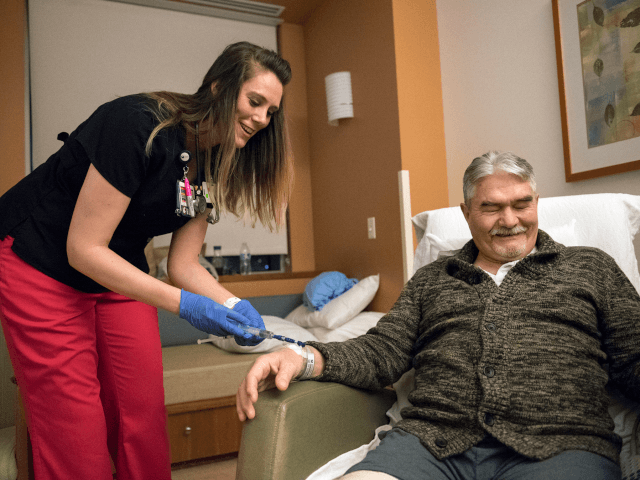 Christina Gay, left, administers medication to Gene Wickstrom of Cathlamet during Gay's April 5, 2018, night shift at Legacy Salmon Creek Medical Center in Vancouver, Washington. Gay studied nursing at Clark College and Washington State University Vancouver. (Photo by Alisha Jucevic/The Columbian via AP)
