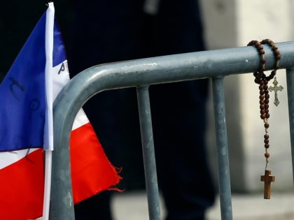 A French flag and a prayer beads are displayed at a makeshift memorial in front of the Saint Etienne church where Priest Jacques Hamel was killed on 26 July in a hostage taking in Saint-Etienne-du-Rouvray, Normandy, France, Thursday, July 28, 2016. The second man who attacked a Normandy church during …
