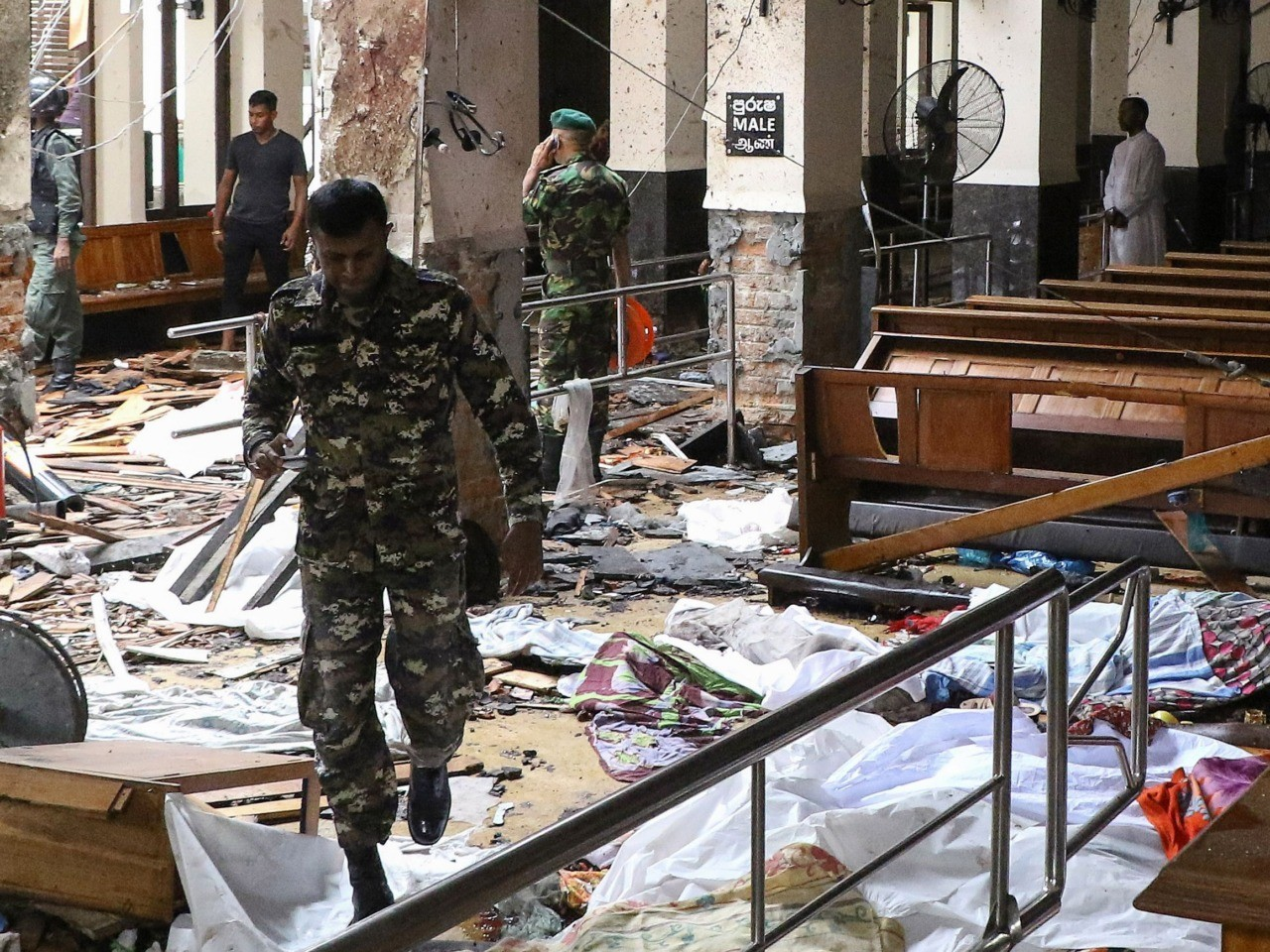 Graphic content / Sri Lankan security personnel walk past dead bodies covered with blankets amid blast debris at St. Anthony's Shrine following an explosion in the church in Kochchikade in Colombo on April 21, 2019. - A string of blasts ripped through high-end hotels and churches holding Easter services in Sri Lanka on April 21, killing at least 156 people, including 35 foreigners. (Photo by ISHARA S. KODIKARA / AFP) (Photo credit should read ISHARA S. KODIKARA/AFP/Getty Images)