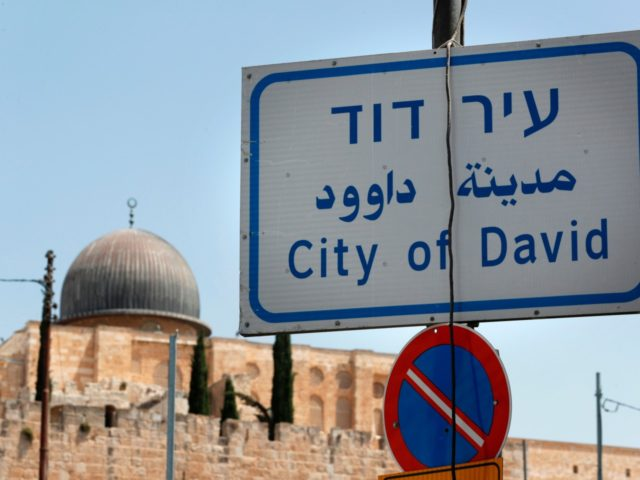 A road sign indicating the City of David, an Israeli settlement and the archaeological site which is speculated to compose the original urban core of ancient Jerusalem is seen near the Jerusalem Old City ramparts and the Al-Aqsa mosque (C), on July 7, 2017. / AFP PHOTO / THOMAS COEX …