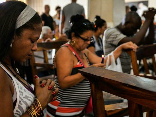 Cuban pilgrims pray at Saint Lazarus Church in El Rincon, Havana, on July 2, 2018 - Saint Lazarus draws together Cuban interconfesional faith in a single figure, and the construction of a new chapel also shows the acceptance of the Catholic Church by the ruling Communist Party. (Photo by YAMIL …
