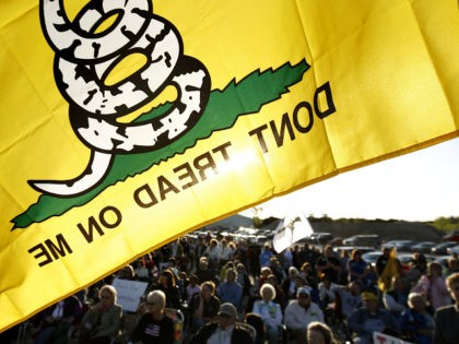 A Don't Tread On Me flag flies over protesters during a rally at Leo O'Laughlin Inc. on the eve of President Barack Obama's visit to Macon, Mo. Tuesday evening, April 27, 2010, in Macon. The protest was organized by the Missouri Republican Party and a tea party group called the …