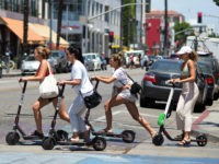 (FILES) In this file photo taken on July 13, 2018, women ride shared electric scooters in Santa Monica, California. - Uber, the ridesharing behemoth set to lauch a stock offering soon, is aiming beyond sharing car rides to becoming the 'Amazon of transportation' in a future where people share instead …