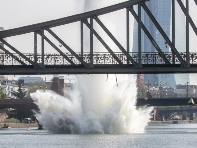A large water fountain rises behind the Iron Bridge when a 250 kilogram US-American bomb from the Second World War in the Main River is detonated with a blast in Frankfurt, Germany, Sunday, April 14, 2019. About 600 people had to leave their homes for security reasons. On the right …