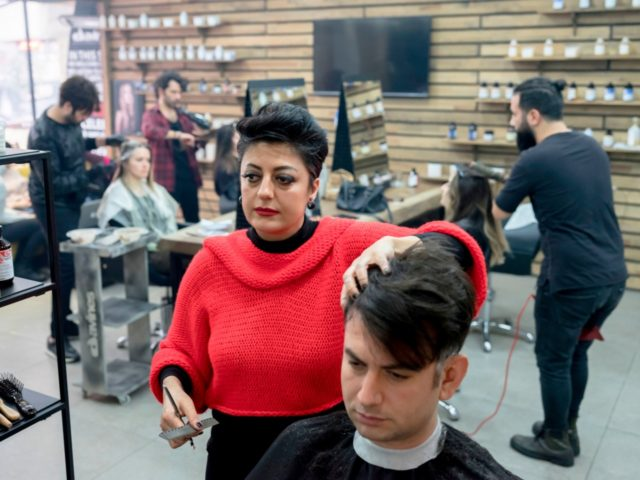 A female men's barber, Serap Aykut (L) works in a barbershop on February 28, 2018, in Istanbul. Serap Aykut has been working as a men's barber for 21 years. / AFP PHOTO / YASIN AKGUL (Photo credit should read YASIN AKGUL/AFP/Getty Images)