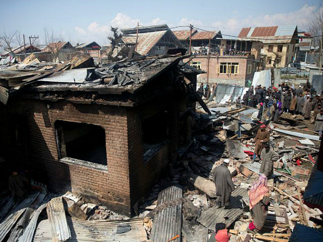 Kashmiri villagers inspect a damaged house after a gun battle in Hajin village, north of Srinagar, Indian controlled Kashmir, Friday, March 22, 2019. Indian security forces killed five militants and an 11-year-old hostage in three separate clashes in the Indian-controlled portion of Kashmir, police and the army said Friday. (AP …
