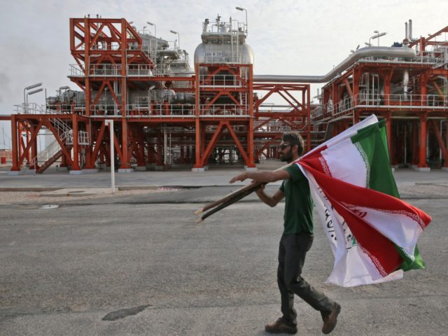 In this Saturday, March 16, 2019 photo, an Iranian worker carries Iranian flags prior to an inauguration ceremony of a natural gas refinery at the South Pars gas field on the northern coast of the Persian Gulf, in Asaluyeh, Iran. On Sunday President Hassan Rouhani inaugurated a new phase in …
