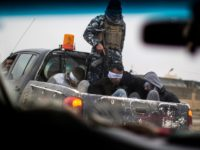 TOPSHOT - Christian militia fighters from the Nineveh Plain Protection Units (NPU) drive a pick-up truck in Qaraqosh (also known as Hamdaniya), transporting four men, allegedly members of the Islamic State (IS) group that were found inside a tunnel in Mosul, on December 20, 2016. / AFP / JM Lopez …