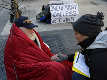 In this Wednesday, Nov. 20, 2013 photo, homeless Korean War veteran Thomas Moore, 79, left, speaks with Boston Health Care for the Homeless street team outreach coordinator Romeena Lee on a sidewalk in Boston. Moore, who said he accidentally killed his best friend with a phosphorous grenade during one firefight …