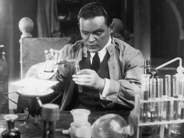 A scientist with staring eyes pours liquid from one test tube to another in a laboratory scene from an unknown German film. (Photo by Hulton Archive/Getty Images)