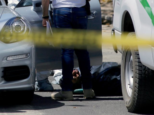 The body of a man shot dead inside his car is removed from the vehicle by forensic personnel in Americana neighbourhood, in the turistic area of Guadalajara, Jalisco State, Mexico, on March 14, 2018. Mexico has suffered a wave of violence linked to drug trafficking that has intensified in recent …