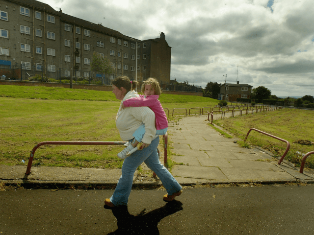 GLASGOW, SCOTLAND - JUNE 16: A young mother carries her child from school in the Barlanark area June 16, 2004 of Glasgow, Scotland. The Barlanark area has been identified in a survey as officially being the most deprived area of Scotland. The study measures deprivation by health, housing, income, unemployment …