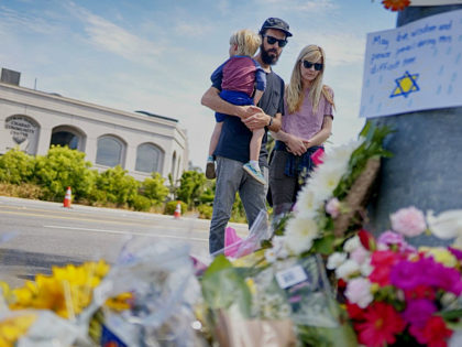 Mourners Troy and Katie McKinney and their son Wynn look over a make-shift memorial across the street from the Chabad of Poway Synagogue on Sunday, April 28, 2019 in Poway, California, one day after a teenage gunman opened fire, killing one person and injuring three others including the rabbi as …