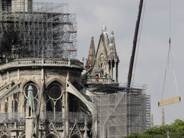 A crane lifts up construction material as scaffoldings surround Notre-Dame Cathedral in Paris on April 17, 2019, two days after a fire that devastated the building in the centre of the French capital. - French President vowed on April 16 to rebuild Notre-Dame cathedral 'within five years', after a fire …
