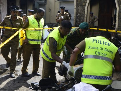 Sri Lankan security personnel and police investigators look through debris outside Zion Church following an explosion in Batticaloa in eastern Sri Lanka on April 21, 2019. - A series of eight devastating bomb blasts ripped through high-end hotels and churches holding Easter services in Sri Lanka on April 21, killing …