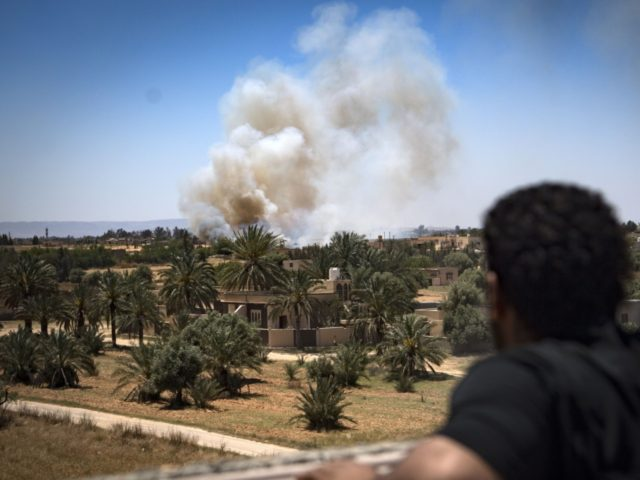 A fighter loyal to the internationally-recognised Government of National Accord (GNA) watches as smoke rises in the distance during clashes with forces loyal to strongman Khalifa Haftar, in Espiaa, about 40 kilometres (25 miles) south of the Libyan capital Tripoli on April 29, 2019. - Fierce fighting for control of …