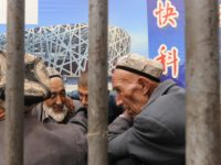 Ethnic Uighur men talk under an Olympic poster in Xinjiang's famed Silk Road city of Kashgar in China's far northwestern, mainly Muslim Xinjiang region on August 6, 2008. Gauging Olympic fervour in this tense city depends on whether you ask a member of the Muslim Uighur ethnic group or a …
