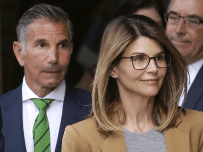 FILE - In this April 3, 2019 file photo, actress Lori Loughlin, front, and husband, clothing designer Mossimo Giannulli, left, depart federal court in Boston after facing charges in a nationwide college admissions bribery scandal. On Tuesday, April 9, Loughlin and Giannulli were among 16 prominent parents indicted on an …