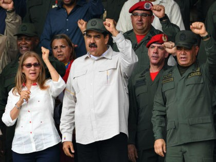 Venezuelan President Nicolas Maduro (2-L), his wife Cilia Flores (L) and Defence Minister Vladimir Padrino (R) gesture during a military parade to commemorate the 17th anniversary of a failed 2002 coup d'état against former leader Hugo Chavez, at Fuerte Tiuna Military Complex, in Caracas on April 13, 2019. (Photo by …