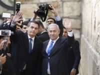 Brazilian President Jair Bolsonaro (L) and Israeli Prime Minister Benjamin Netanyahu wave to the press during a visit to the Western wall, the holiest site where Jews can pray, in the Old City of Jerusalem on April 1, 2019. - Bolsonaro visited the Western Wall alongside Netanyahu today, becoming the …