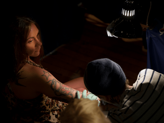 A tattooist works on the hand of a girl during the 15th Annual Tattooing Convention in Manhattan in New York. AFP PHOTO / MLADEN ANTONOV (Photo credit should read MLADEN ANTONOV/AFP/GettyImages)